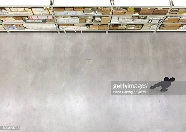 High Angle View Of Person Walking On Passage At Warehouse