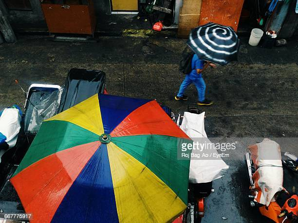 High Angle View Of Person Walking On Road With Umbrella