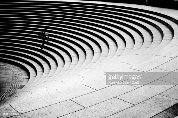 high angle view of person walking on spiral staircase - spiral stock pictures, royalty-free photos & images