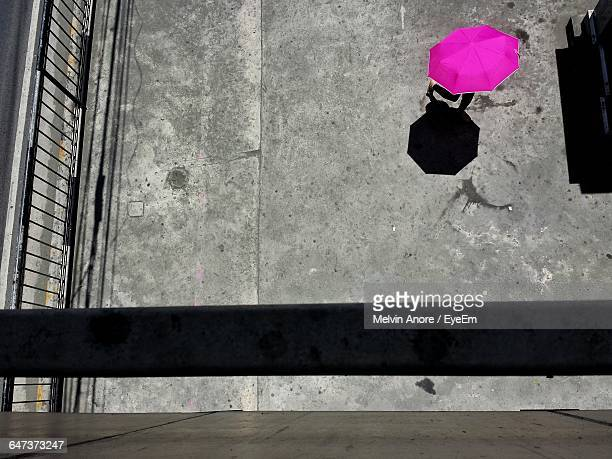 High Angle View Of Person Walking With Pink Umbrella At Street On Sunny Day