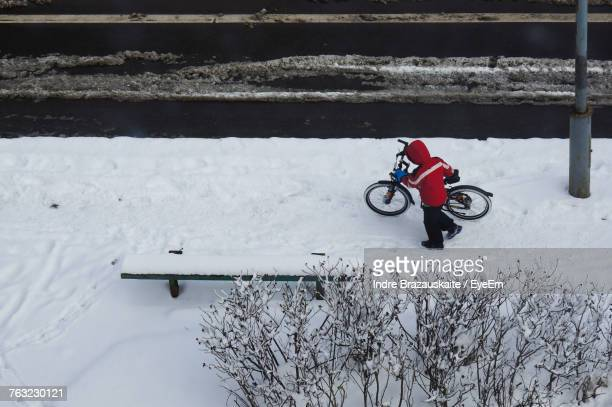 High Angle View Of Person With Bicycle On Snow