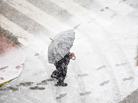 High angle view of person with umbrella walking in snow on street  with red umbrella in snowstorm. Valencia, Spain - gettyimageskorea