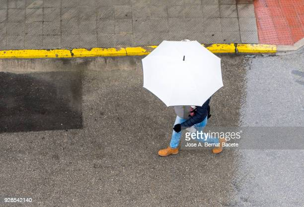 high angle view of person with umbrella walking in the rain on street with white umbrella and with a baby in the rucksack .valencia, spain - umbrella stock photos and pictures