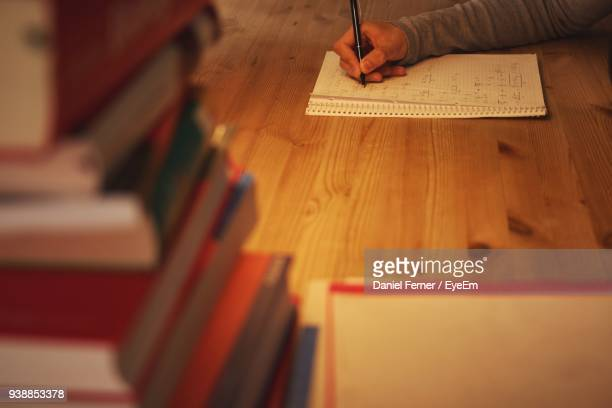 High Angle View Of Person Writing On Book At Table