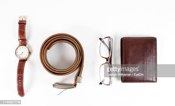 high angle view of personal accessories against white background - leather belt stock pictures, royalty-free photos & images