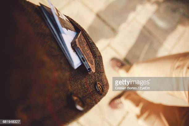 high angle view of phone and book in pocket with man standing in background - bortes stock pictures, royalty-free photos & images