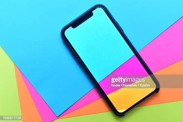 high angle view of phone cover on multi colored papers - phone cover stock pictures, royalty-free photos & images
