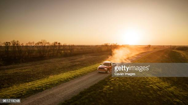 high angle view of pick-up truck moving on road amidst field - rushing the field stock pictures, royalty-free photos & images