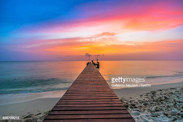 high angle view of pier on sandy beach during sunset - cancun stock pictures, royalty-free photos & images