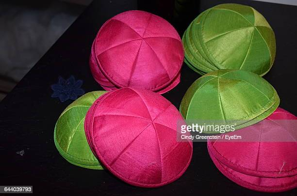 High Angle View Of Pink And Green Yarmulkes On Table