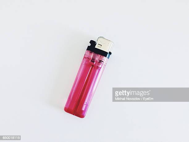 High Angle View Of Pink Cigarette Lighter Against White Background