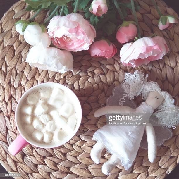 high angle view of pink flowers with doll and hot chocolate in basket on table - candy dolls fotografías e imágenes de stock