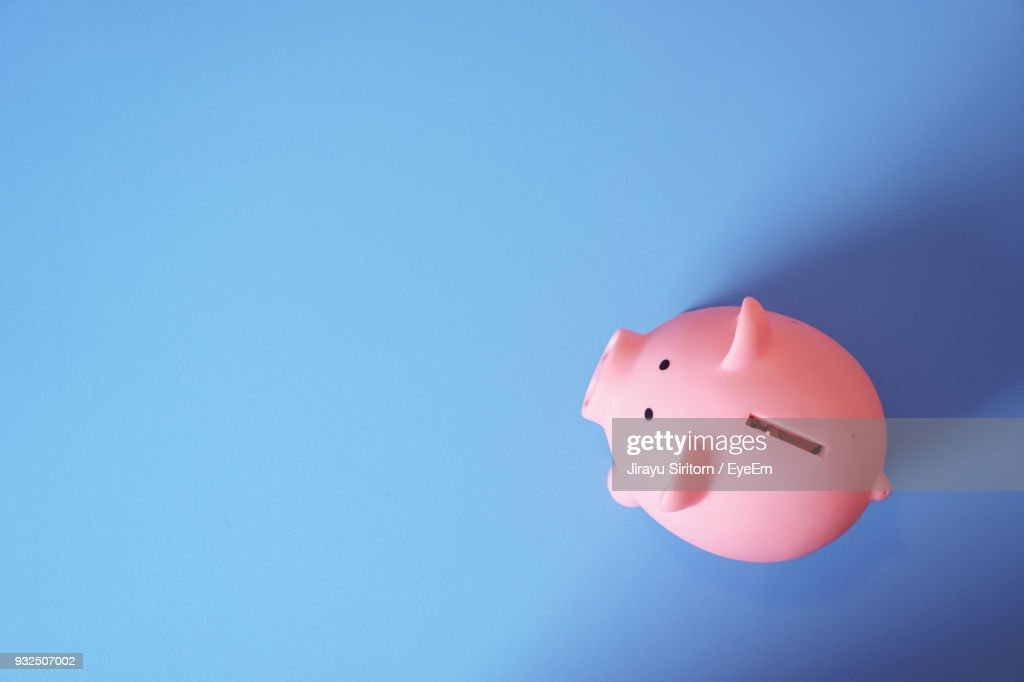 High Angle View Of Pink Piggy Bank On Blue Background : Foto de stock