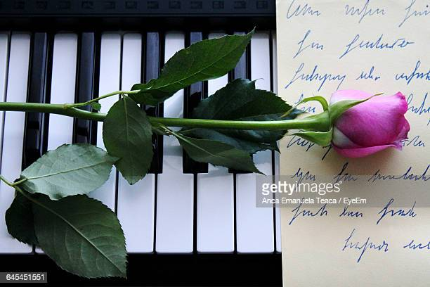 High Angle View Of Pink Rose And Letter On Piano