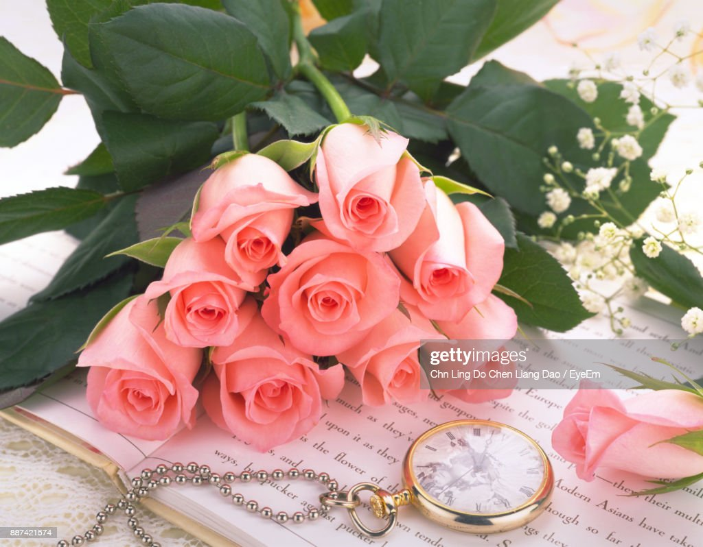 High angle view of pink rose bouquet by pocket watch on table stock high angle view of pink rose bouquet by pocket watch on table stock photo izmirmasajfo Gallery