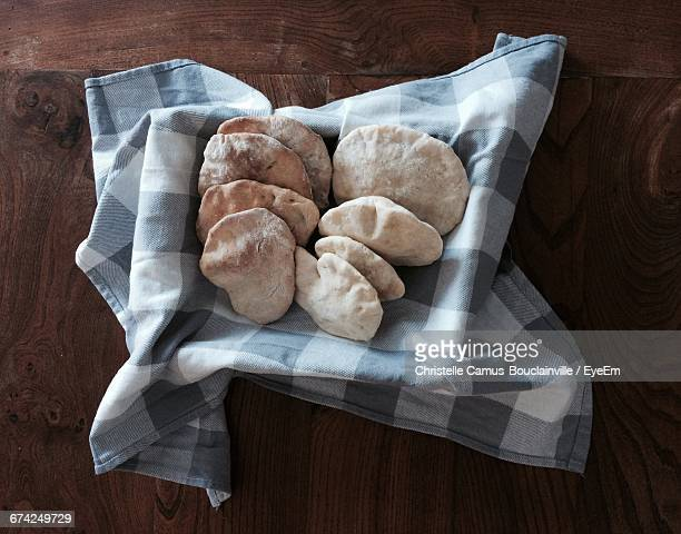 High Angle View Of Pita Bread In Container On Wooden Table