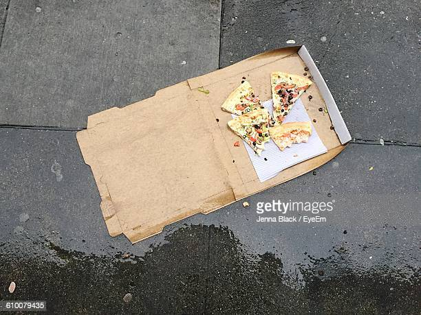 High Angle View Of Pizza In Box On Wet Floor During Rainy Season