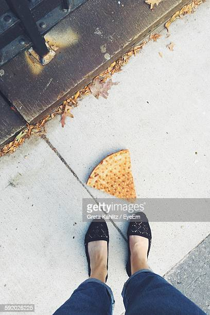 High Angle View Of Pizza On Street By Low Section Of Woman