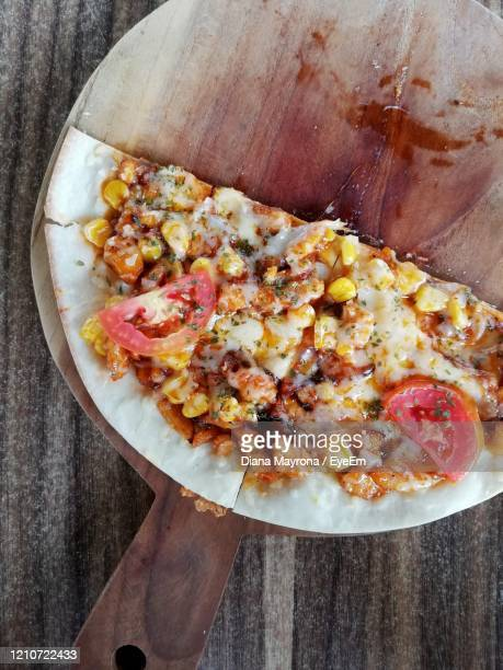 high angle view of pizza on table - kalimantan stock pictures, royalty-free photos & images