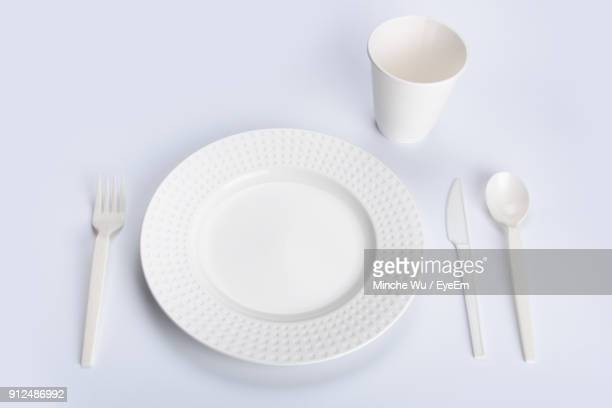 high angle view of plastic plate and spoons with disposable cup over white background - plastic plate stock photos and pictures
