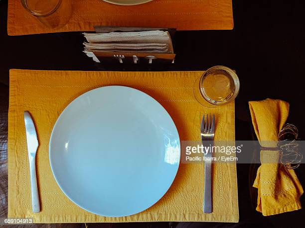 High Angle View Of Plate On Napkin Over Dining Table