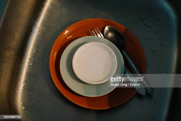 High Angle View Of Plates In Kitchen Sink At Home