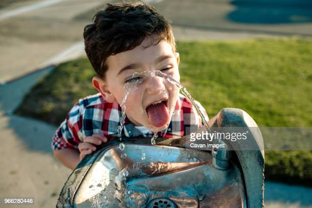 high angle view of playful boy drinking water from fountain - durst stock-fotos und bilder