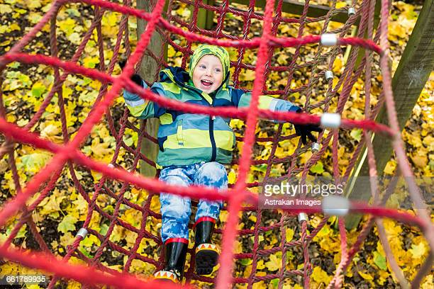 High angle view of playful boy in rope netting during obstacle course at forest
