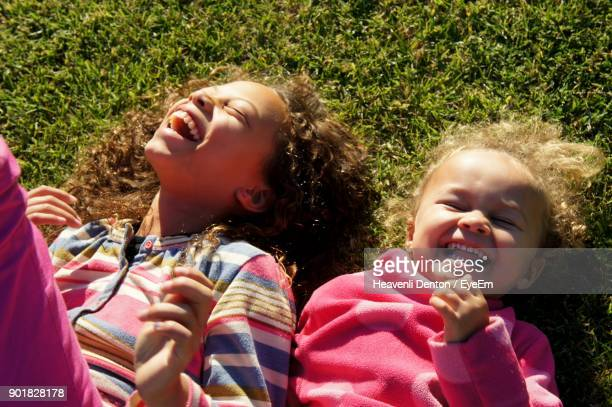 High Angle View Of Playful Sisters Lying On Grassy Field