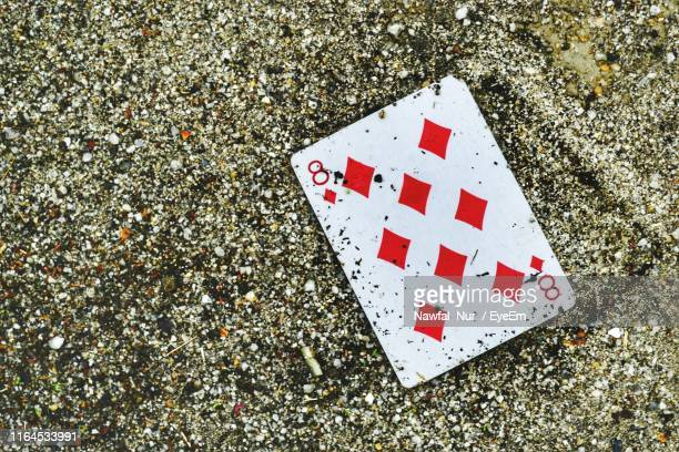 high angle view of playing card on sand at beach - nawfal nur stock pictures, royalty-free photos & images