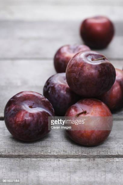 high angle view of plums on wooden table - ワインレッド ストックフォトと画像
