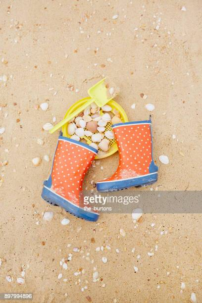 High Angle View of Polka dot gumboots, shovel, sieve and shells on the beach