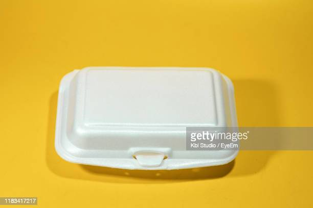 high angle view of polystyrene container over yellow background - polystyrene stock pictures, royalty-free photos & images