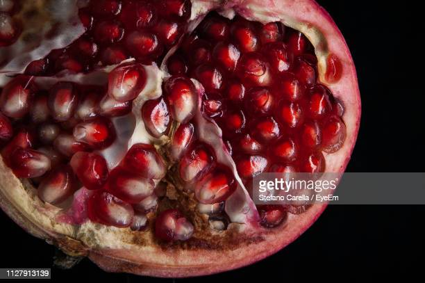 high angle view of pomegranate on black background - ripe stock pictures, royalty-free photos & images