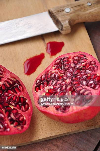 high angle view of pomegranate on cutting board - nathalie pellenkoft stock pictures, royalty-free photos & images