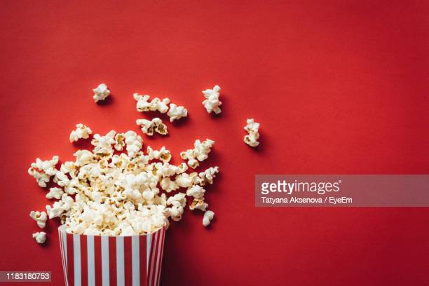 high angle view of popcorn spilling from container over red background - ポップコーン ストックフォトと画像