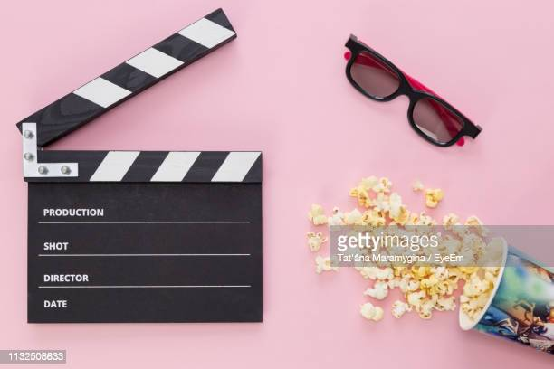 high angle view of popcorn with film slate and sunglasses on pink background - film stock pictures, royalty-free photos & images