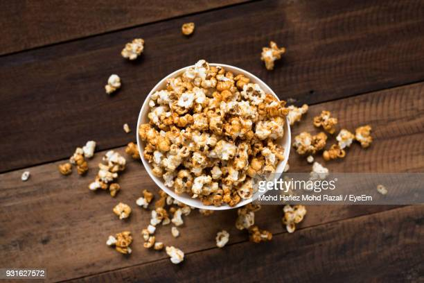 High Angle View Of Popcorns In Bowl On Wooden Table
