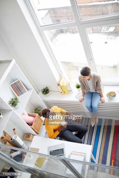 High angle view of positive young multi-ethnic colleagues in casual clothing drinking coffee and chatting in modern office