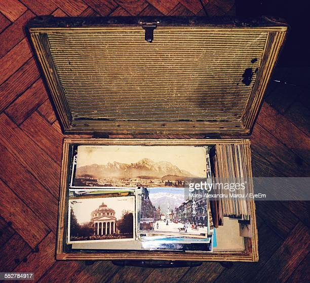 High Angle View Of Postcards In Suitcase On Table