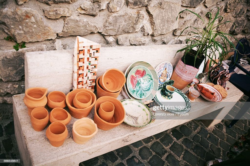 High Angle View Of Pots And Plates Displayed On Table Outdoors : Stock Photo