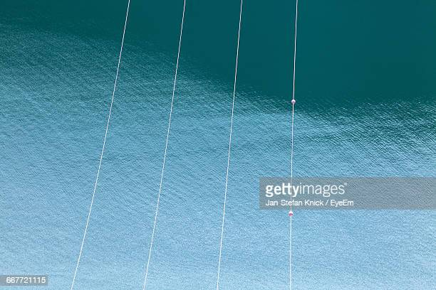 High Angle View Of Power Lines Against Sea Water