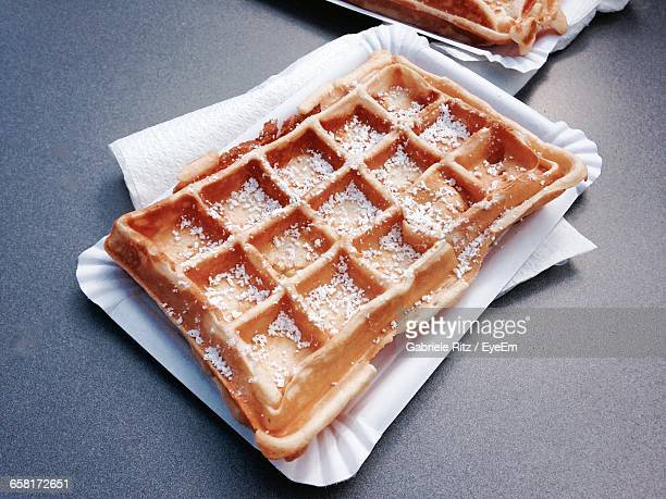 High Angle View Of Powered Sugar Waffel On Paper Plate