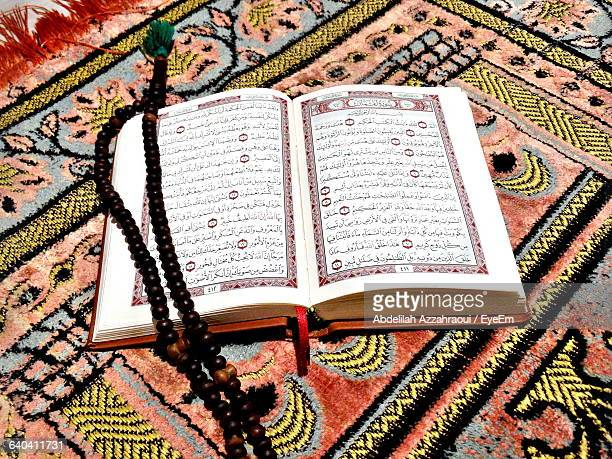 High Angle View Of Prayer Beads On Koran