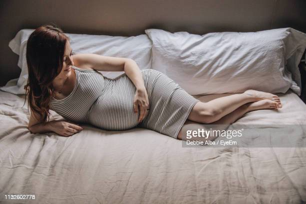high angle view of pregnant woman lying on bed at home - lying on side stock pictures, royalty-free photos & images