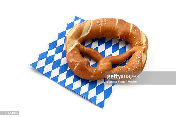 High Angle View Of Pretzel And Paper Over White Background