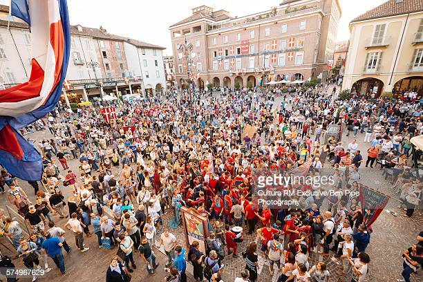 High angle view of procession and crowds in town square at Palio di Asti medieval festival, Asti, Piedmont, Italy