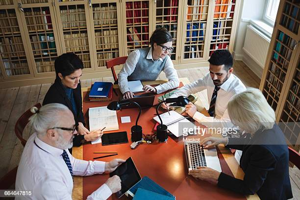 High angle view of professionals working at table in law library