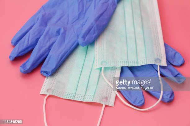 high angle view of protective gloves and masks on table - purple glove stock pictures, royalty-free photos & images