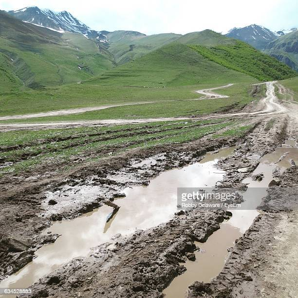 high angle view of puddles on dirt road leading towards mountains - mud stock pictures, royalty-free photos & images